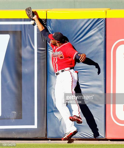 Jason Heyward of the Atlanta Braves collides with the wall as he misplays a fly ball hit by Mike Fontenot of the San Francisco Giants during Game...