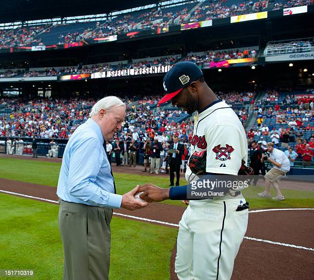 Jason Heyward of the Atlanta Braves gives the ceremonial first pitch ball to Chairman Emeritus of the Atlanta Braves Bill Bartholomay before the...