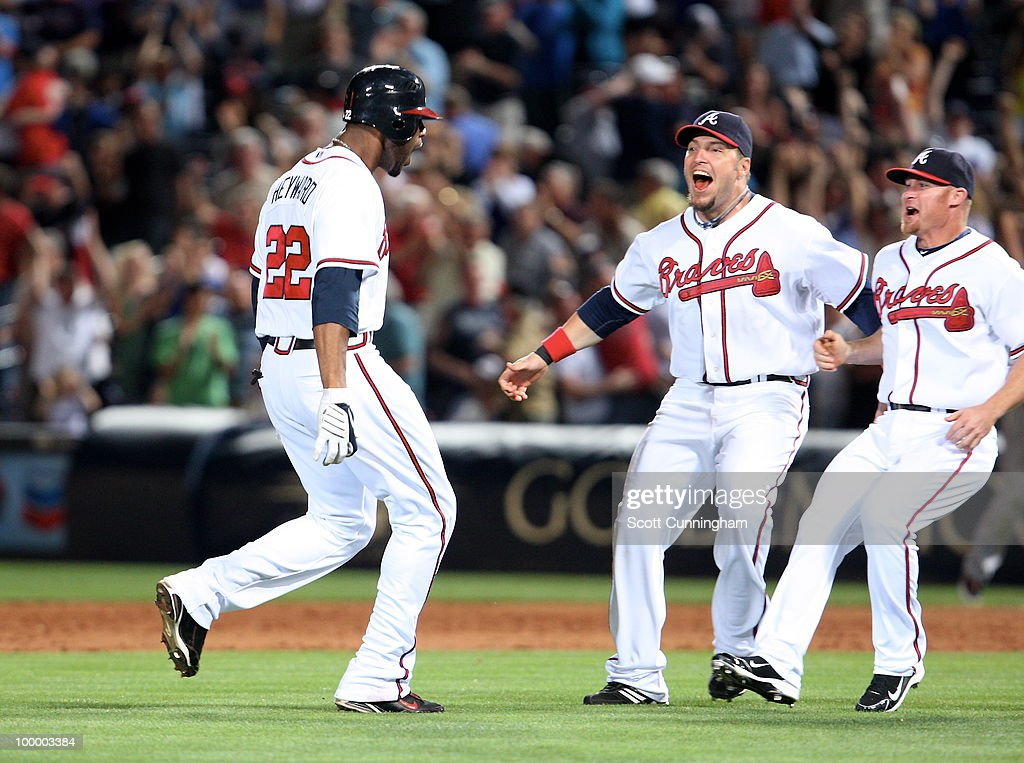 Jason Heyward #22 of the Atlanta Braves is congratulated by Eric Hinske #20 and Brooks Conrad #26 after knocking in the game-winning run against the Cincinnati Reds at Turner Field on May 19, 2010 in Atlanta, Georgia. The Braves defeated the Reds 5-4.
