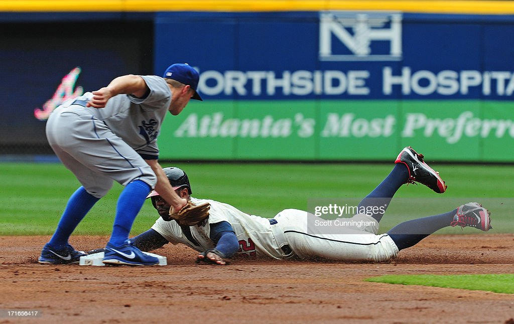 Jason Heyward #22 of the Atlanta Braves is tagged out on a steal attempt by Mark Ellis #14 of the Los Angeles Dodgers at Turner Field on May 19, 2013 in Atlanta, Georgia.