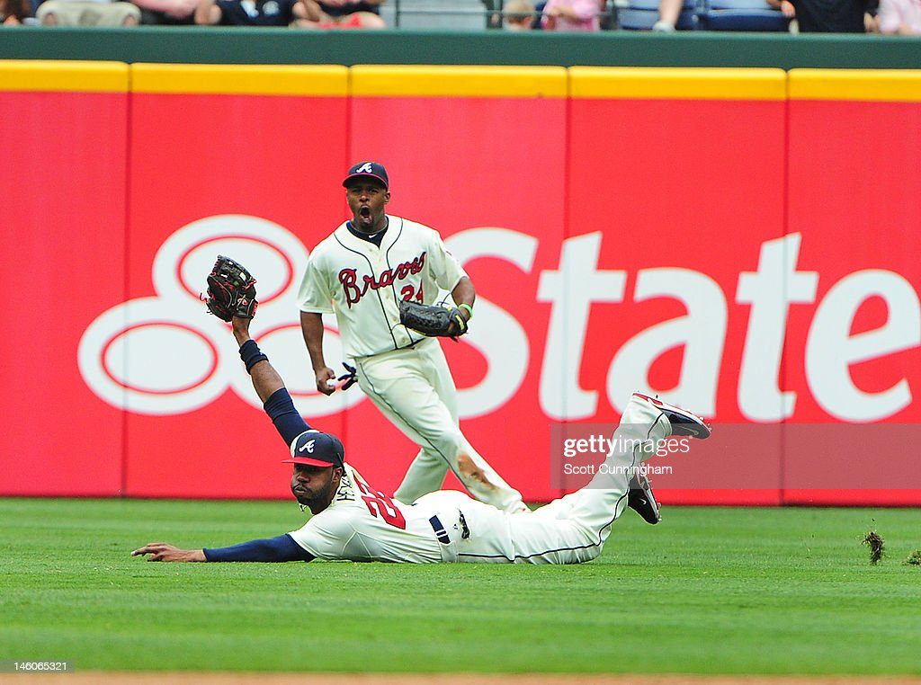Jason Heyward #22 of the Atlanta Braves makes a diving catch as Michael Bourn #24 reacts during the game against the Toronto Blue Jays at Turner Field on Jue 9, 2012 in Atlanta, Georgia.