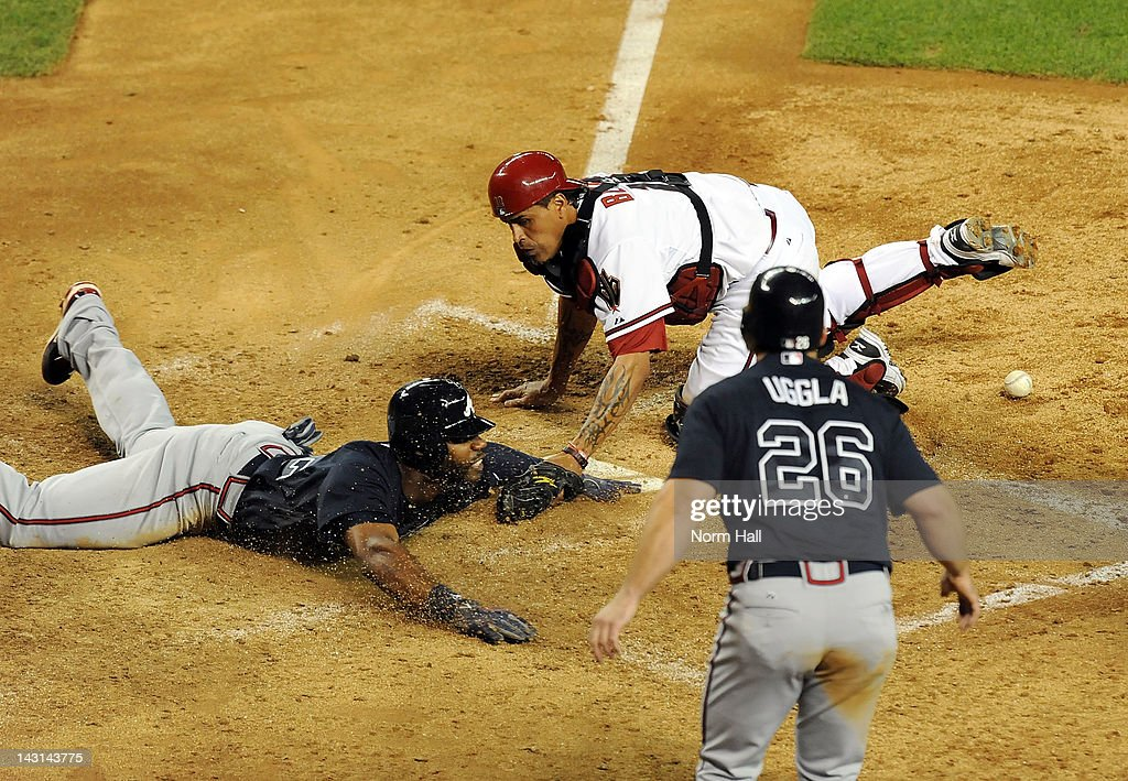 Jason Heyward #22 of the Atlanta Braves slides safely into home as Henry Blanco #12 applies the tag without the ball at Chase Field on April 19, 2012 in Phoenix, Arizona.