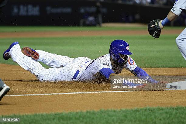 Jason Heyward of the Chicago Cubs dives into third base after hitting a triple in the second inning against the Los Angeles Dodgers during game one...