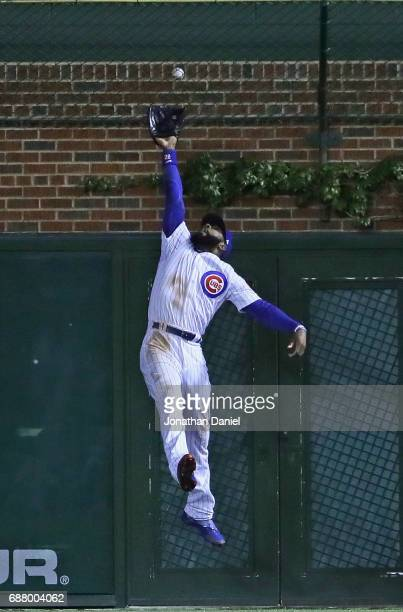 Jason Heyward of the Chicago Cubs leaps in vain for a home run ball hit by Mac Williamson of the San Francisco Giants that lands in the basket in the...