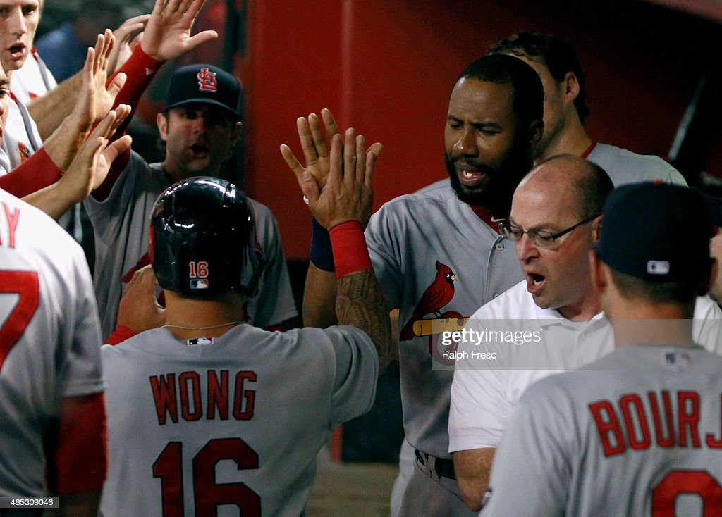 Jason Heyward #22 of the St Louis Cardinals (R) congratulates teammate Kolten Wong #16 after Wong scores against the Arizona Diamondbacks during the seventh inning of a MLB game at Chase Field on August 26, 2015 in Phoenix, Arizona. The Cardinals defeated the Diamondbacks 3-1.