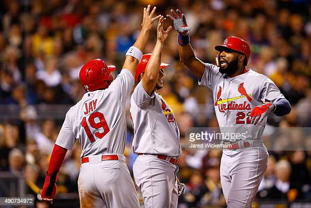 Jason Heyward of the St Louis Cardinals is congratulated at home plate by teammate Jon Jay after hitting a grand slam home run in the third inning...