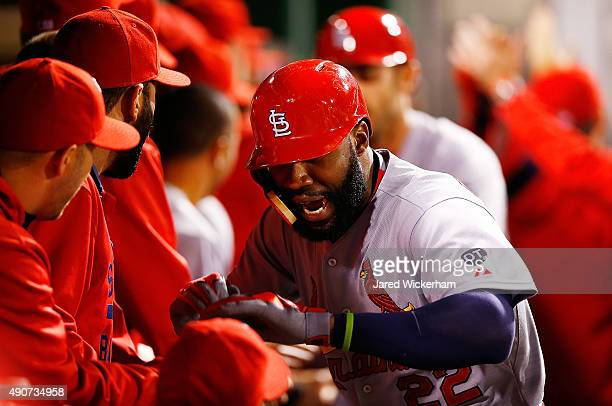 Jason Heyward of the St Louis Cardinals is congratulated by teammates in the dugout after hitting a grand slam home run in the third inning against...