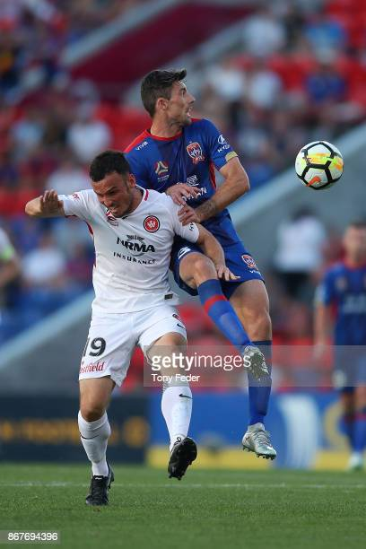 Jason Hoffman of the Jets contests the ball with Mark Bridge of the Wanderers during the round four ALeague match between the Newcastle Jets and the...