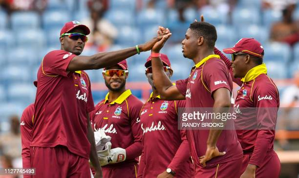 Jason Holder and Oshane Thomas of West Indies celebrate the dismissal of Joe Root of England during the 4th ODI between West Indies and England at...