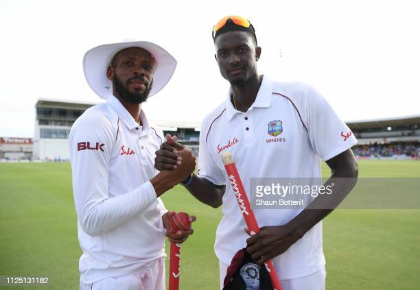 Jason Holder and Roston Chase celebrate after Day Four of the First Test match between England and West Indies at Kensington Oval on January 26, 2019...