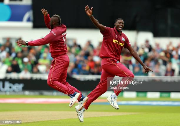 Jason Holder of the West Indies celebrates with team mate Andre Russell after taking the wicket of Imad Wasim during the Group Stage match of the ICC...