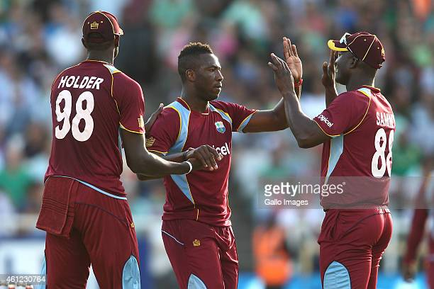 Jason Holder of the West Indies congratulates Andre Russell of the West Indies and West Indies captain Darren Sammy for getting South African captain...