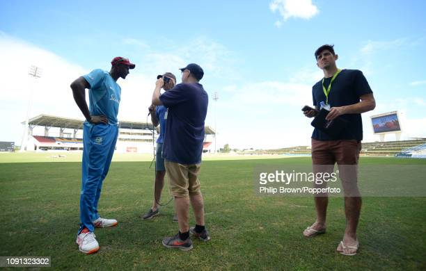 Jason Holder of the West Indies is interviewed as Sir Alastair Cook looks on after a training session at the Sir Vivian Richards Stadium before the...