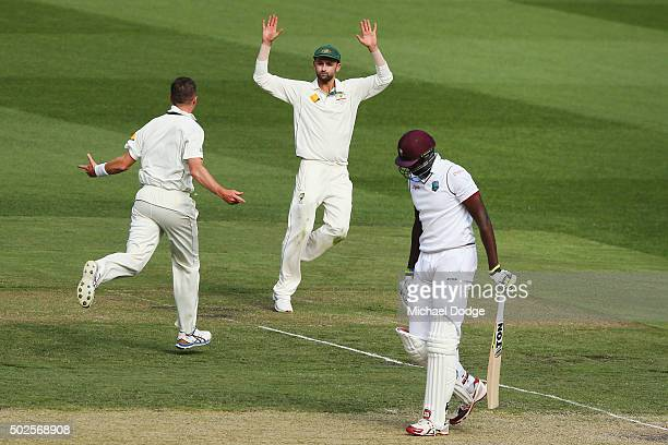 Jason Holder of the West Indies walks off after being bowled by Peter Siddle of Australia who celebrates wth Nathan Lyon during day two of the Second...