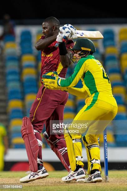 Jason Holder of West Indies hits 4 and Alex Carey of Australia watch during the 2nd ODI between West Indies and Australia at Kensington Oval,...