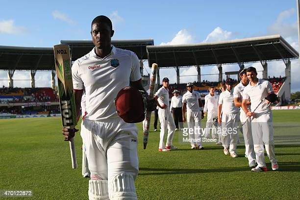 Jason Holder of West Indies raises his bat at the end of the drawn match after being undefeated on 103 runs during day five of the 1st Test match...
