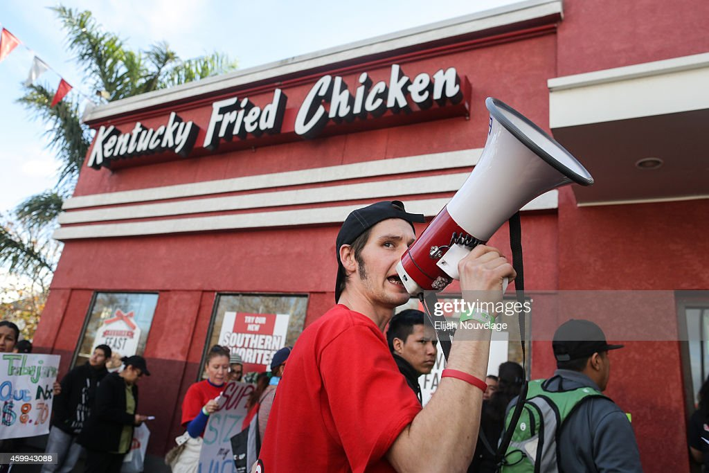 Jason Hughes of Hayward leads a chant during a demonstration for higher wages for fast food workers at a Kentucky Fried Chicken on December 4, 2014 in Oakland, California. The protest was part of a nationwide day of demonstrations for higher wages and the right to unionize.