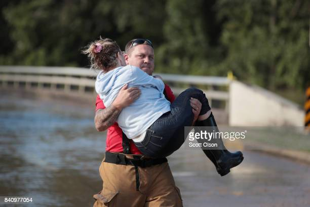 Jason Hunt a firefighter from Arkadelphia Arkansas carries a woman to dry ground after she was rescued from her apartment complex when it was...