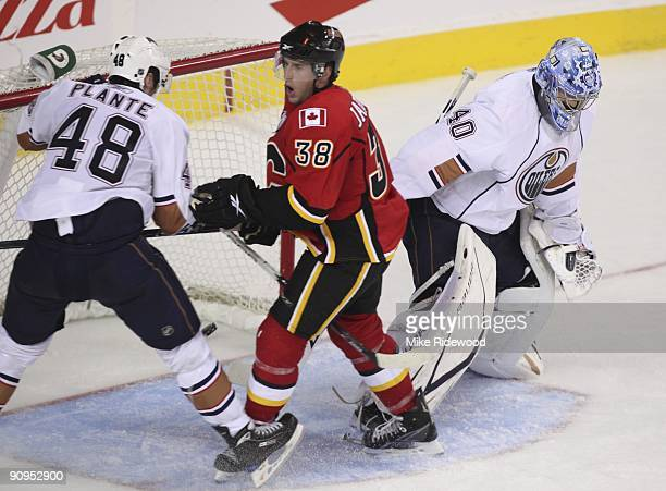 Jason Jaffray of the Calgary Flames celebrates his goal in front of Alex Plante and Devan Dubnyk of the Edmonton Oilers in the third period of NHL...