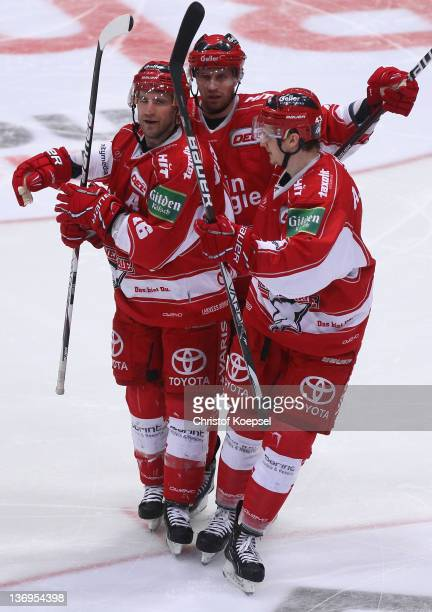 Jason Jaspers of Koelner Haie celebrates the second goal with Alexander Weiss and Torsten Ankert during the DEL match between Koelner Haie and EHC...