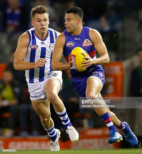 Jason Johannisen of the Bulldogs is chased by Shaun Higgins of the Kangaroos during the 2015 AFL round 22 match between the North Melbourne Kangaroos...