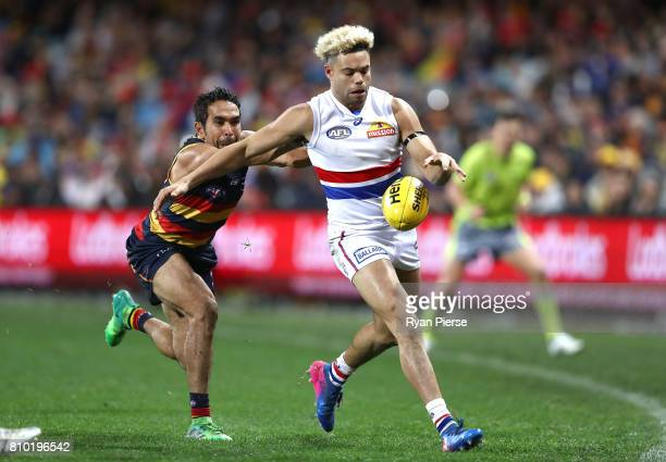 Jason Johannisen of the Bulldogs kicks despite pressure from Eddie Betts of the Crows during the round 16 AFL match between the Adelaide Crows and...
