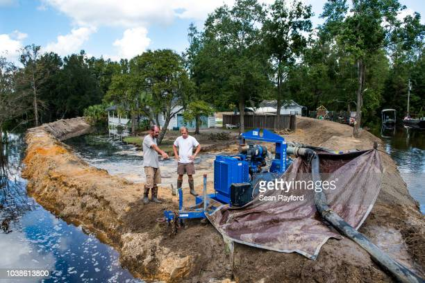 Jason Johnson left and homeowner Archie Sanders work to build a temporary levee to hold back floodwaters caused by Hurricane Florence near the...