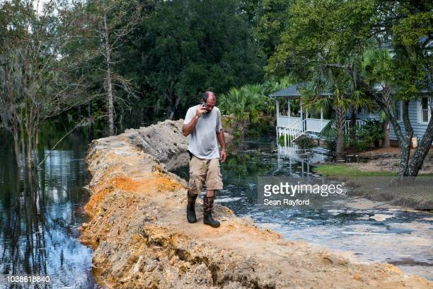 Jason Johnson walks on a temporary levee to hold back floodwaters caused by Hurricane Florence near the Waccamaw River on September 23, 2018 in...