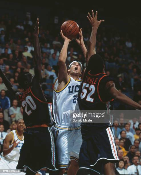 Jason Kapono, Forward for the University of California, Los Angeles UCLA Bruins shoots for the hoop over Will Kimble and Terrance Johnson of the...