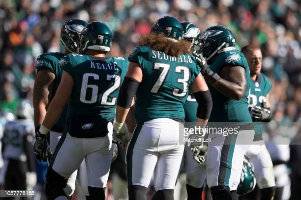 Jason Kelce, Isaac Seumalo, and Jason Peters of the Philadelphia Eagles huddle against the Carolina Panthers at Lincoln Financial Field on October...