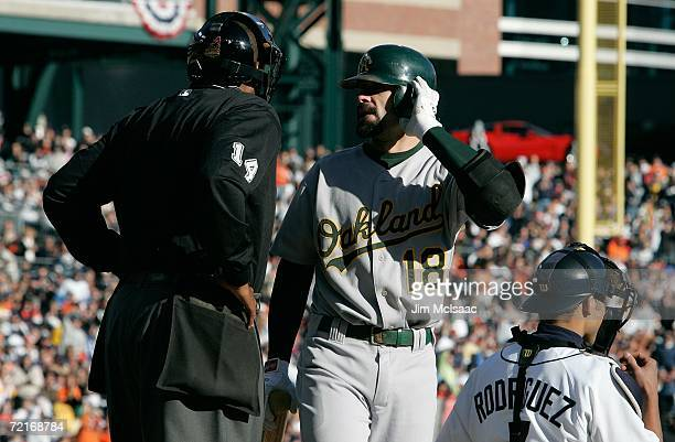 Jason Kendall of the Oakland Athletics talks with home plate umpire Chuck Meriwether after Kendall struck out looking against the Detroit Tigers...