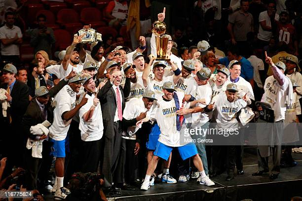 Jason Kidd of the Dallas Mavericks holds up the Larry O'Brien Championship trophy as he celebrates with his teammates head coach Rick Carlisle and...