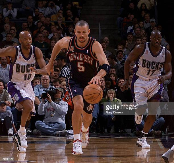Jason Kidd of the New Jersey Nets dribbles upcourt in front of Sam Cassell and Anthony Mason of the Milwaukee Bucks during a game at the Bradley...