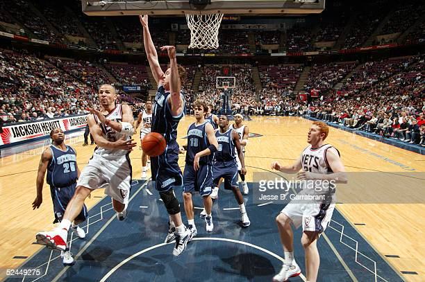 Jason Kidd of the New Jersey Nets passes the ball around Ben Handlogten of the Utah Jazz to Brian Scalabrine of the Nets on March 18 2005 at the...