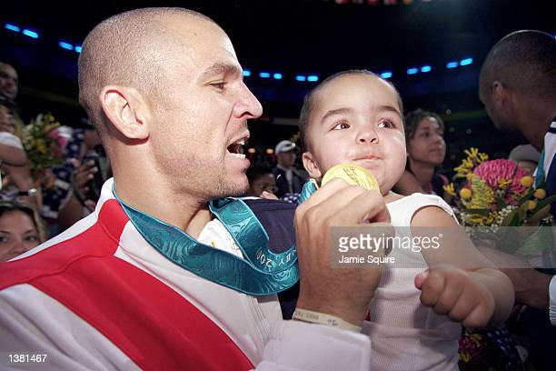 Jason Kidd of the USA shows his gold medal to his son after capturing the gold in the men's basketball game against France at the Sydney SuperDome...