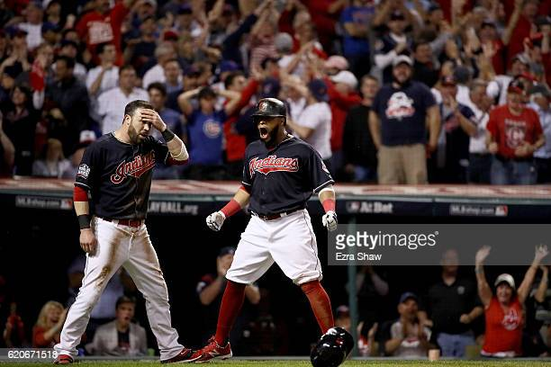 Jason Kipnis and Carlos Santana of the Cleveland Indians celebrate after scoring runs on a wild pitch thrown by Jon Lester of the Chicago Cubs during...