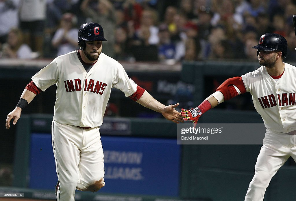 Jason Kipnis #22 of the Cleveland Indians celebrates with Nick Swisher #33 after scoring on a single by Lonnie Chisenhall #8 (not pictured) against the Texas Rangers during the sixth inning of their game on August 2, 2014 at Progressive Field in Cleveland, Ohio.