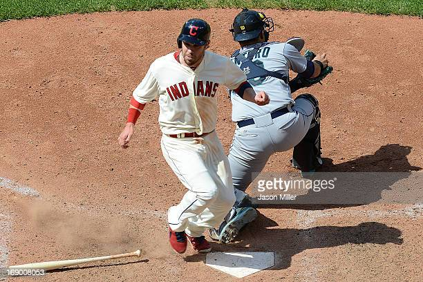 Jason Kipnis of the Cleveland Indians scores to win the game as catcher Jesus Montero of the Seattle Mariners fails to keep his foot on the plate...