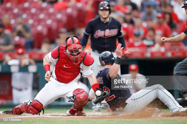 Jason Kipnis of the Cleveland Indians slides at home plate ahead of the throw to Tucker Barnhart of the Cincinnati Reds after a single by Greg Allen...