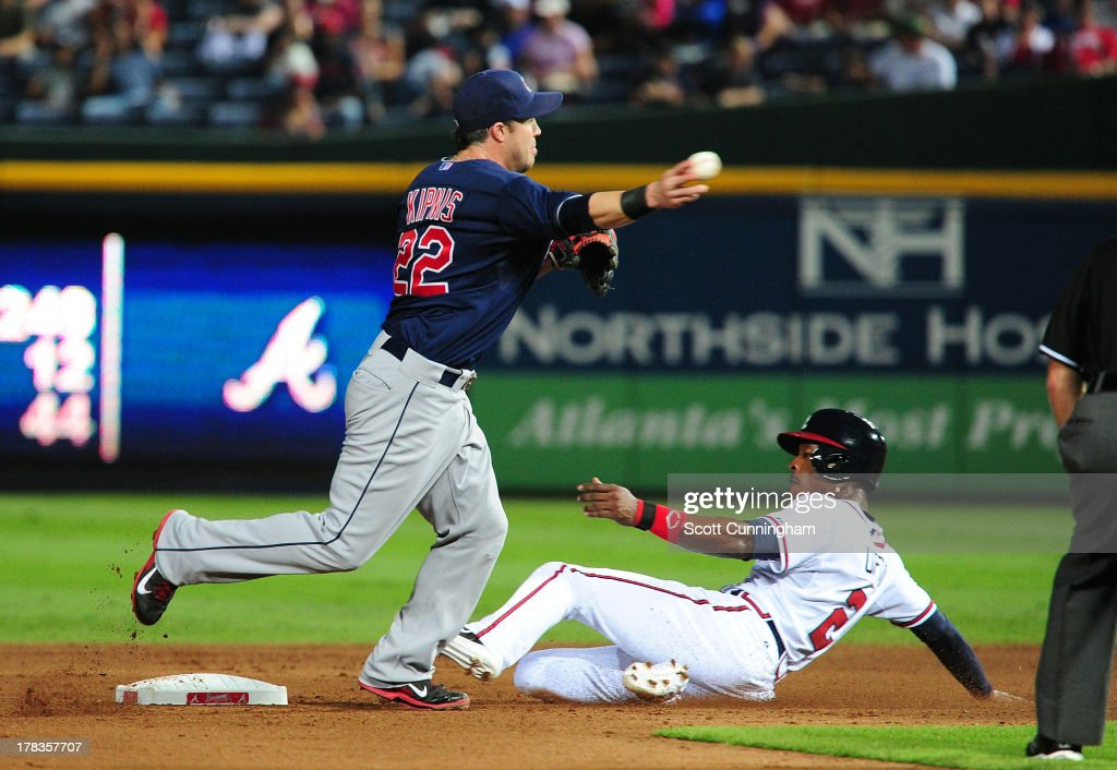 Jason Kipnis #22 of the Cleveland Indians turns a double play against B. J. Upton #2 of the Atlanta Braves at Turner Field on August 29, 2013 in Atlanta, Georgia.
