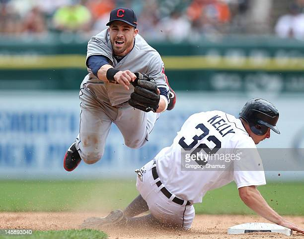 Jason Kipnis of the Cleveland Indians turns a double play in the eighth inning around the slide of Don Kelly of the Detroit Tigers at Comerica Park...