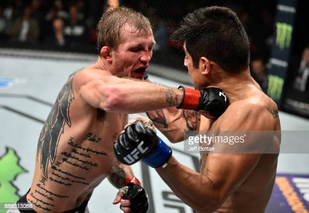 Jason Knight punches Gabriel Benitez of Mexico in their featherweight bout during the UFC Fight Night event inside Save Mart Center on December 9...