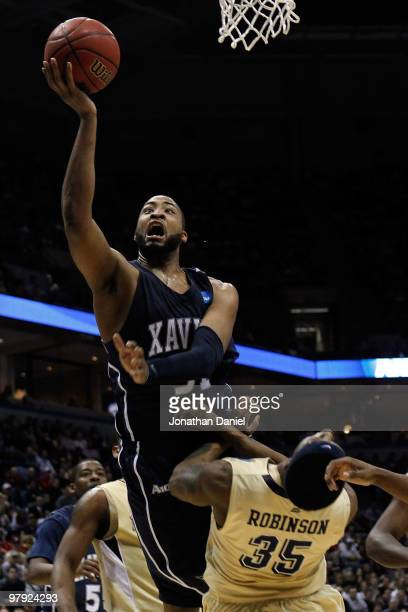 Jason Love of the Xavier Musketeers goes up for a shot as he crashes into Nasir Robinson of the Pittsburgh Panthers in the second half during the...