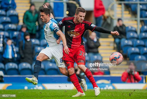 Jason Lowe of Blackburn Rovers and Gylfi Sigurosson of Swansea City battle for the ball during the FA Cup Fourth Round match between Blackburn Rovers...