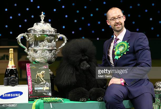 Jason Lynn with Ricky the Standard Poodle, as they celebrate winning the Best in Show category of Crufts 2013 during the final day at Crufts Dog Show...