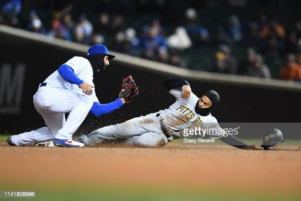 Jason Martin of the Pittsburgh Pirates beats the tag of Javier Baez of the Chicago Cubs to steal second base during the seventh inning at Wrigley...