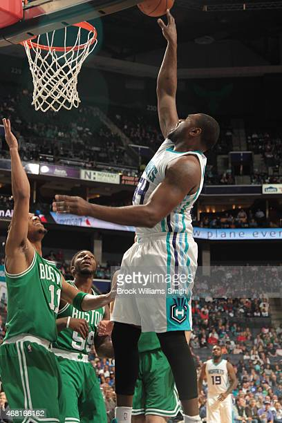 Jason Maxiell of the Charlotte Hornets shoots against Evan Turner of the Boston Celtics during the game at the Time Warner Cable Arena on March 30...