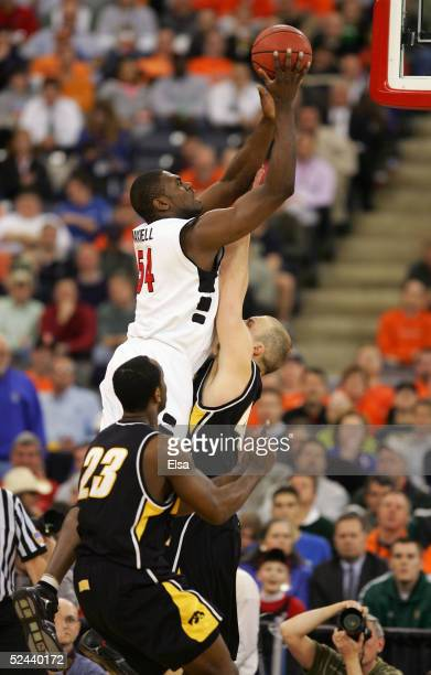 Jason Maxiell of the Cincinnati Bearcats attempts a shot against Greg Brunner and Doug Thomas of the Iowa Hawkeyes in the first round game of the...