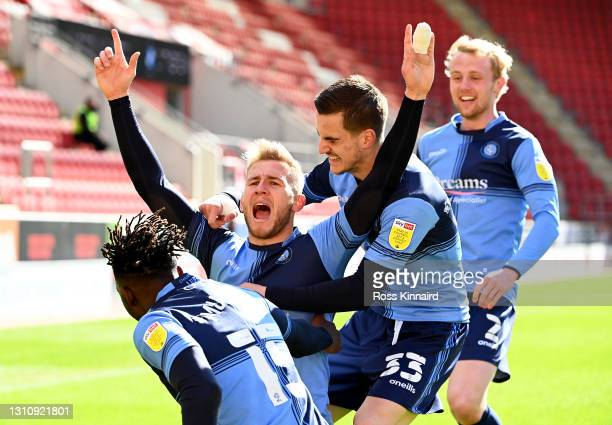 Jason McCarthy of Wycombe Wanderers celebrates with teammates Anis Mehmeti, Jack Grimmer and Admiral Muskwe after scoring their team's second goal...