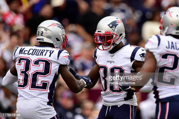 Jason McCourty of the New England Patriots celebrates with his teammates against the Washington Redskins during the second quarter in the game at...